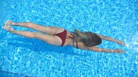 B?sta sikt av oigenk?nnlig kvinnasimning under vatten i p?l med genomskinligt klart vatten Ung flicka som kopplar av under lager videofilmer