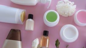 Bästa sikt av olika hygieniska/kosmetiska produkter och blommor på ny rosa bakgrund Wellnessskönhetbehandling arkivfilmer