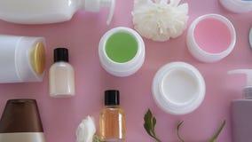 Bästa sikt av olika hygieniska/kosmetiska produkter och blommor på ny rosa bakgrund Wellnessskönhetbehandling lager videofilmer