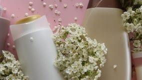 Bästa sikt av olika hygieniska produkter och blommor på ny rosa bakgrund Wellnessskönhetbehandling lager videofilmer