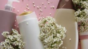 Bästa sikt av olika hygieniska produkter och blommor på ny rosa bakgrund Wellnessskönhetbehandling arkivfilmer