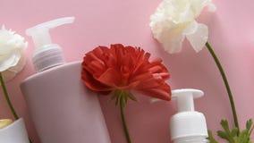 Bästa sikt av olika hygieniska produkter och blommor på ny rosa bakgrund Wellnessskönhetbehandling stock video