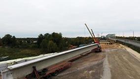 Bästa sikt av område för brokonstruktion med två kranar närliggande körbana och fält stock video