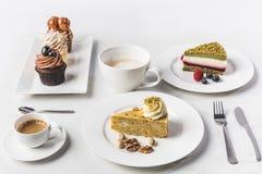 Bästa sikt av ordningen av stycken av olika kakor på plattor, koppar kaffe och muffin Fotografering för Bildbyråer