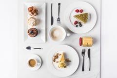 Bästa sikt av ordningen av stycken av olika kakor på plattor, koppar kaffe och muffin Royaltyfri Bild
