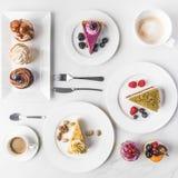 Bästa sikt av ordningen av stycken av olika kakor på plattor, koppar kaffe och muffin Royaltyfri Fotografi
