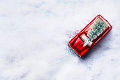 Bästa sikt av på den retro bilen för röd leksak med den gröna julgranen i snö Idérikt julferiebegrepp arkivfoto