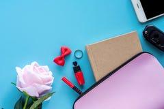 Bästa sikt av påsen för rosa dam med dagbokboken, pennan, läppstift, pilbågen, cirkeln, biltangent, smartphonen och den söta rose royaltyfria foton