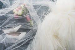 bästa sikt av par av skor, bröllopsklänningen och buketten på trämörker arkivfoto