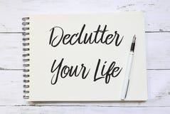 Bästa sikt av pennan och anteckningsboken som är skriftliga med Declutter ditt liv på träbakgrund arkivbild