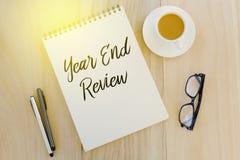 Bästa sikt av pennan, solglasögon, en kopp kaffe och anteckningsboken som är skriftliga med årsslutgranskning på träbakgrund arkivfoto