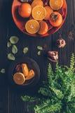 Bästa sikt av persimoner med klippta apelsiner och granatäpplen Arkivbilder
