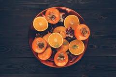 Bästa sikt av persimoner med klippta apelsiner och granatäpplen på plattan Royaltyfri Fotografi