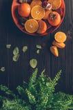 Bästa sikt av persimoner med klippta apelsiner och granatäpplen på plattan och den gröna växten Arkivbilder