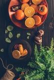 Bästa sikt av persimoner med klippta apelsiner och granatäpplen på plattor Royaltyfri Foto