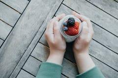 Bästa sikt av pojkehänder med pudding med chiafrö, yoghurt och f royaltyfria bilder