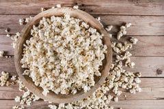 Bästa sikt av popcorn i träbunke och retro lantligt skrivbord arkivfoto