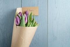 Bästa sikt av purpurfärgade tulpan i hantverkpapper på blå wood bakgrund med 8 kortet för marsch Royaltyfri Foto