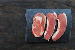 Bästa sikt av rå nötköttbiff på trämörk bakgrund, matkött eller grillfest royaltyfri foto