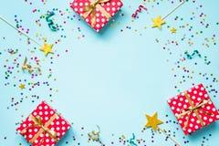 Bästa sikt av röda prickiga askar för en gåva, guld- trollspön, färgrika konfettier och band över blå bakgrund isolerad white för royaltyfri foto