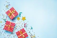 Bästa sikt av röda prickiga askar för en gåva, guld- trollspön, färgrika konfettier och band över blå bakgrund isolerad white för arkivfoto