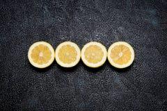 Bästa sikt av raden av klippta citroner på svart bakgrund Royaltyfri Foto