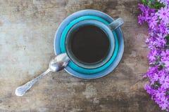 Bästa sikt av rosa färgblommor, den blåa koppen kaffe och en tappningsked på gammal trälantlig tabellbakgrund royaltyfria foton