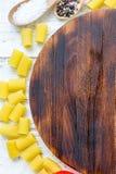 Bästa sikt av skärbrädan med pasta och grönsaker omkring med stället för din text Arkivbilder