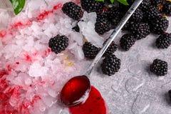 Bästa sikt av skinande vita iskuber Is med mogna björnbär, efterrättskeden och bärsirap på en grå stenbakgrund Royaltyfri Fotografi