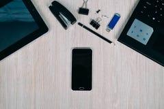Bästa sikt av skrivbordet med grejer och apparater Arkivbilder