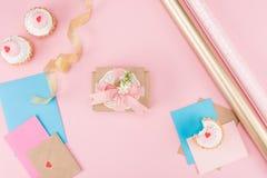Bästa sikt av smakliga muffin, tomma kort, det dekorativa kuvertet och inpackningspapper på rosa färger Arkivbilder
