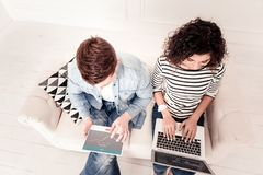 Bästa sikt av smarta ungdomarsom sitter på soffan royaltyfria bilder
