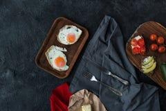Bästa sikt av stekte ägg och smakliga sunda mellanmål för frukost Royaltyfria Bilder