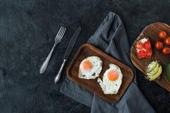 Bästa sikt av stekte ägg och sunda mellanmål för frukost Arkivbilder