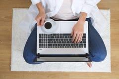Bästa sikt av studentflickan som surfar internet, online-shopping på bärbara datorn och mobiltelefonen och att rymma debitering/k arkivfoton
