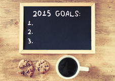 Bästa sikt av svart tavla med målen för uttryck 2015 över träbräde med coffe och kakor arkivfoton