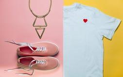 Bästa sikt av t-skjorta och rosa färgskor för vit kvinna på rosa färg- och gulingbakgrund Modekläder- och tillbehöruppsättning Le Arkivfoton