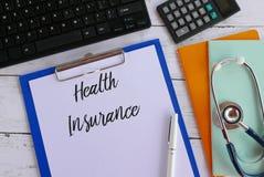 Bästa sikt av tangentbordet, räknemaskinen, böcker, stetoskopet, pennan, skrivplattan och papper som är skriftliga med sjukförsäk arkivfoto