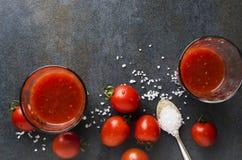 Bästa sikt av tomatfruktsaft, nya körsbärsröda tomater och att salta på det mörka köksbordet arkivbild
