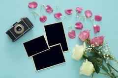 Bästa sikt av tomma fotoramar bredvid gamla kamera och rosor Royaltyfria Bilder