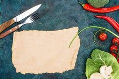 Bästa sikt av tomt pergament, gaffeln med kniven och mogna rå grönsaker Royaltyfri Bild