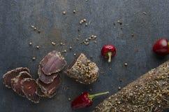 Bästa sikt av torkat kött med röd peppar på den mörka tabellen arkivfoto