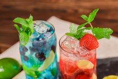 Bästa sikt av två ljusa alkoholiserade coctailar med mintkaramellen, limefrukt, is, jordgubbar på träbakgrunden Sommardrycker Royaltyfri Foto