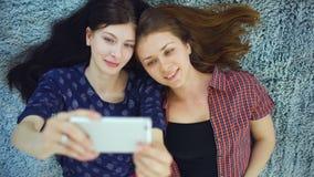 Bästa sikt av två nätta flickor i pyjamas som gör selfieståenden på säng i sovrum hemmastadd arkivfilmer
