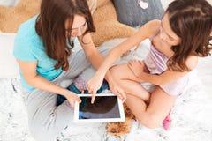 Bästa sikt av två systrar som tillsammans använder minnestavlan för tom skärm fotografering för bildbyråer