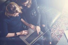 Bästa sikt av två unga flickor som arbetar på datoren och använder mobila enheter Kvinna som bär den svarta sweatern och sitter p Royaltyfri Fotografi