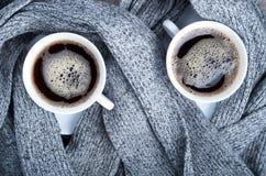 Bästa sikt av två vita koppar med den varma kaffe och grå färghalsduken Royaltyfria Bilder