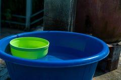 Bästa sikt av tvål i plast- korg och borsten för tvätteri med den pålagda plast- flaskan av schampo det konkreta golvet i ett sol arkivbilder