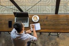 Bästa sikt av unga asiatiska affärsmanhandstilanmärkningar royaltyfri bild