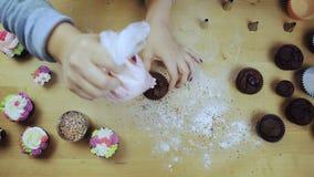 Bästa sikt av unga kvinnlighänder som dekorerar den chokladmuffin eller muffin med kräm, genom att använda bakelsepåsen för denna lager videofilmer